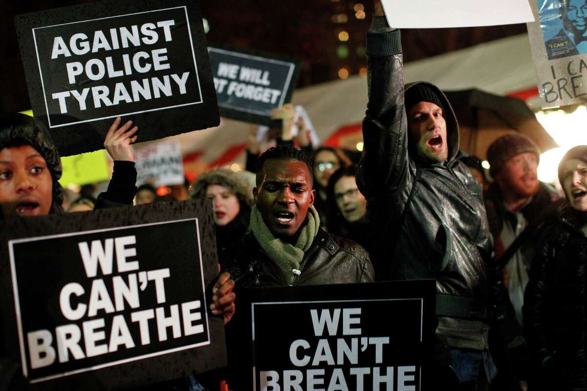 Protesters rallying against a grand jury's decision not to indict the police officer involved in the death of Eric Garner gather in Columbus Circle, Friday, Dec. 5, 2014, in New York. (AP Photo/Jason DeCrow)