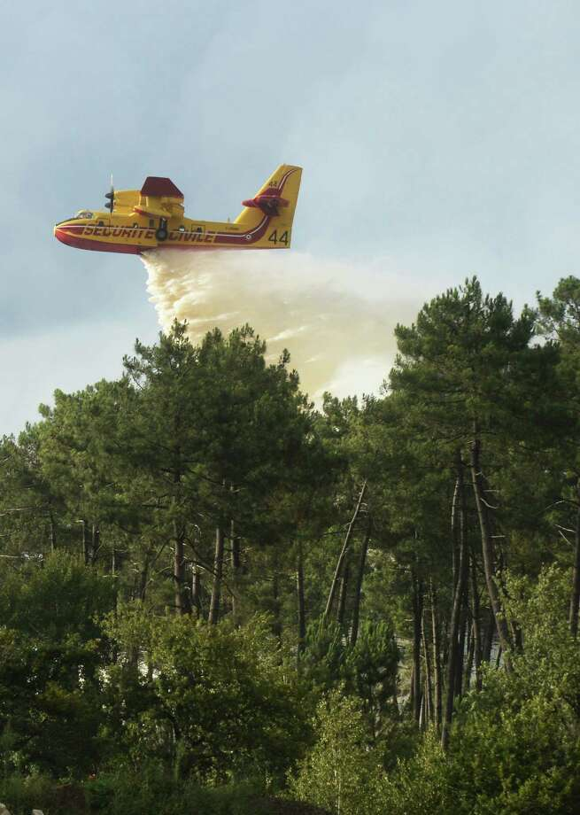 A Canadair water bomber aircraft drops water as firefighters try to extinguish a forest fire that broke out near Saint-Jean d'Illac, some 20km of Bordeaux, on July 24, 2015. Firefighters and Canadair water bomber aircrafts are battling to control several wildfires that have burned around 340 hectares of pine forest in the Gironde region.  AFP PHOTO / MEHDI FEDOUACHMEHDI FEDOUACH/AFP/Getty Images Photo: MEHDI FEDOUACH, Staff / AFP / Getty Images / AFP