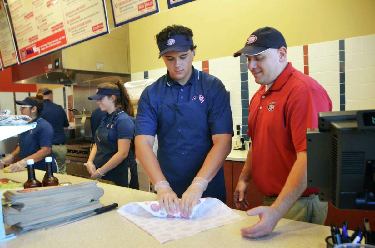 Area General Manager, John Stefanidis, right, oversees as Arthur Delibero, from Ansonia, wraps a sandwich at Jersey Mike's Subs on Thursday, July 23, 2015 in Derby, Conn.