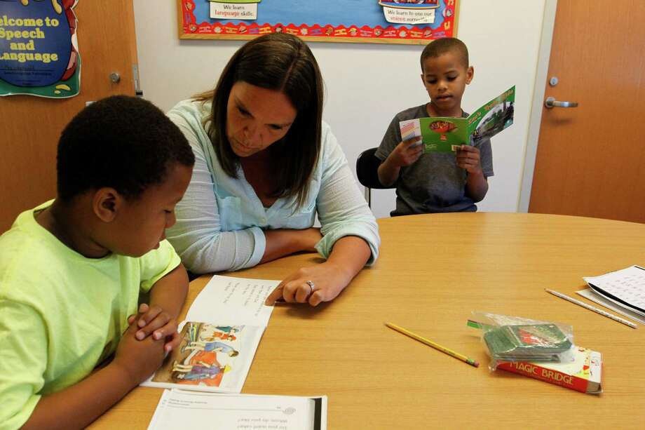 Sarah Perez, a first grade teacher at Old Greenwich School works with Calijah Joseph and K'den Batts during a Horizons at Brunswick School summer program in Greenwich on Monday, June 23, 2015. Photo: Matthew Brown / For Hearst Connecticut Media / Connecticut Post Freelance