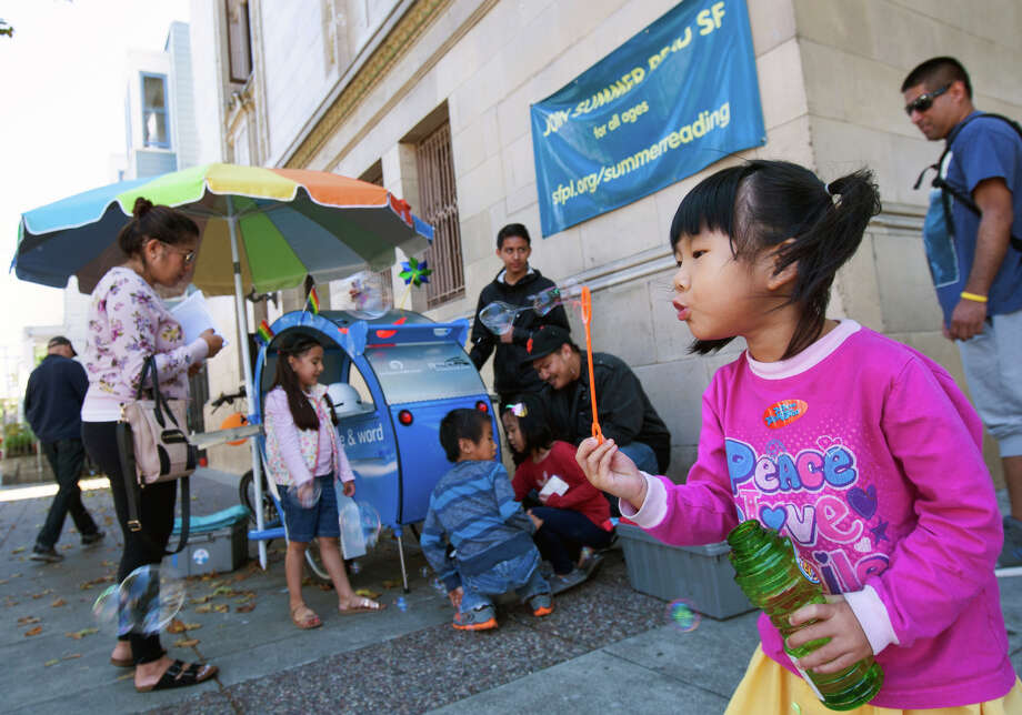 Fiona Lam, 4, blows bubbles during a visit by the Spoke & Word bike to the library's Mission Branch. Photo: Santiago Mejia / Photos By Santiago Mejia / Special To The Chronicle / ONLINE_YES