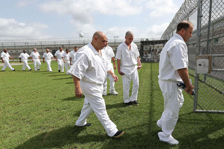 Veterans exit a commons area after a flag-lowering ceremony at the jail. Most of the men in the veterans program are in the jail for the final months of their confinement. Photo: JERRY LARA /San Antonio Express-News / © 2015 San Antonio Express-News