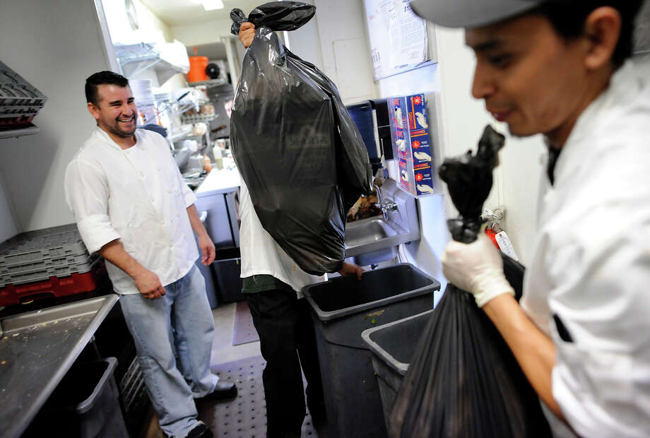 Chef Wilson Mendez (left) watches as dishwasher Max Rodas (right) and another worker take out the garbage at Luka's Taproom, where the owner says the monthly trash bill soared from $1,350 to $2,250. Photo: Michael Short / Michael Short / Special To The Chronicle / ONLINE_YES