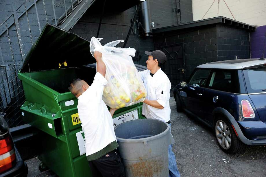Chef Wilson Mendez, right, and dishwasher Max Rodas throw bags of trash into a single landfill dumpster in the back of Luka's Taproom in Oakland, CA Friday, July 24 2015.   Because of a significant rate increase for collection in Oakland, Luka's Taproom has decided to stop composting their food waste and instead put all their trash into a landfill dumpster. Photo: Michael Short / Special To The Chronicle / ONLINE_YES