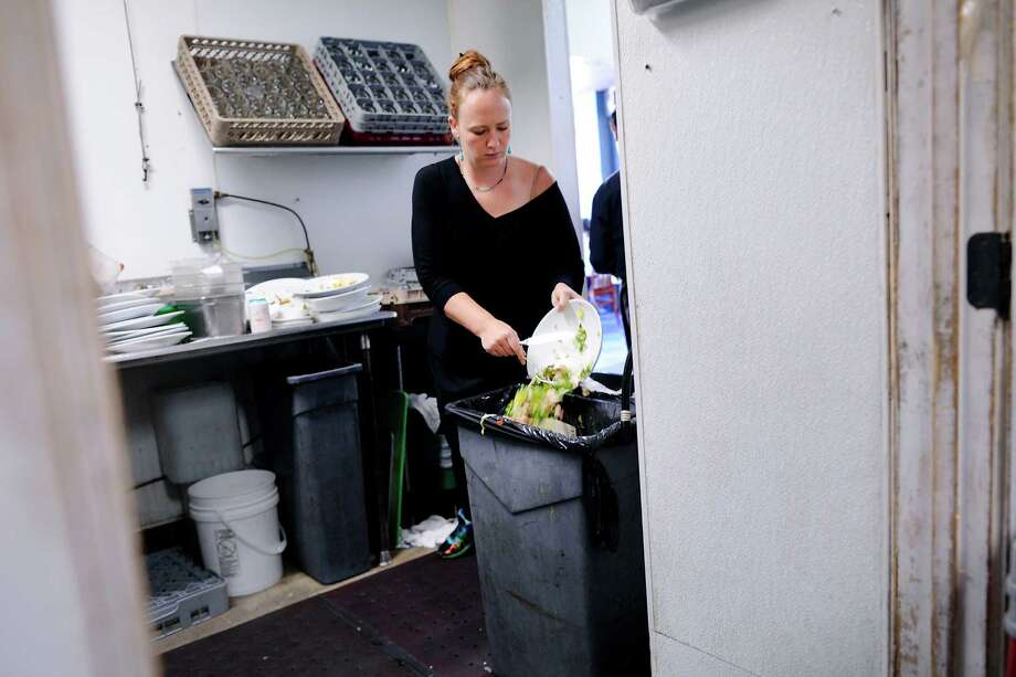 Server Carmen Anderson scrapes leftover food into a trash in the kitchen at Luka's Taproom in Oakland, CA Friday, July 24 2015.   Because of a significant rate increase for collection in Oakland, Luka's Taproom has decided to stop composting their food waste and instead put all their trash into a landfill dumpster. Photo: Michael Short / Special To The Chronicle / ONLINE_YES