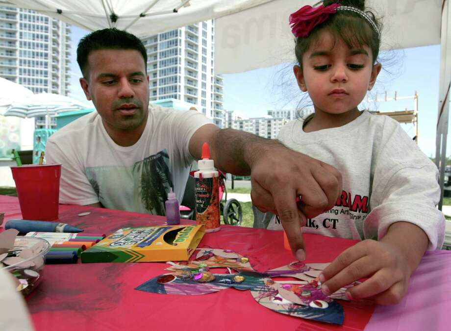From left, Samie Seyal of Fairfield, helps his daughter, Inaya, 3, design a mask during the first Stamford Art Festival in Stamford on Saturday, June 25, 2015. More than 100 artisans showed works in ceramics, jewelry, wearable art and other fine arts and crafts which continues on Sunday, July 26 at Harbor Point. Photo: Matthew Brown / For Hearst Connecticut Media / Connecticut Post Freelance
