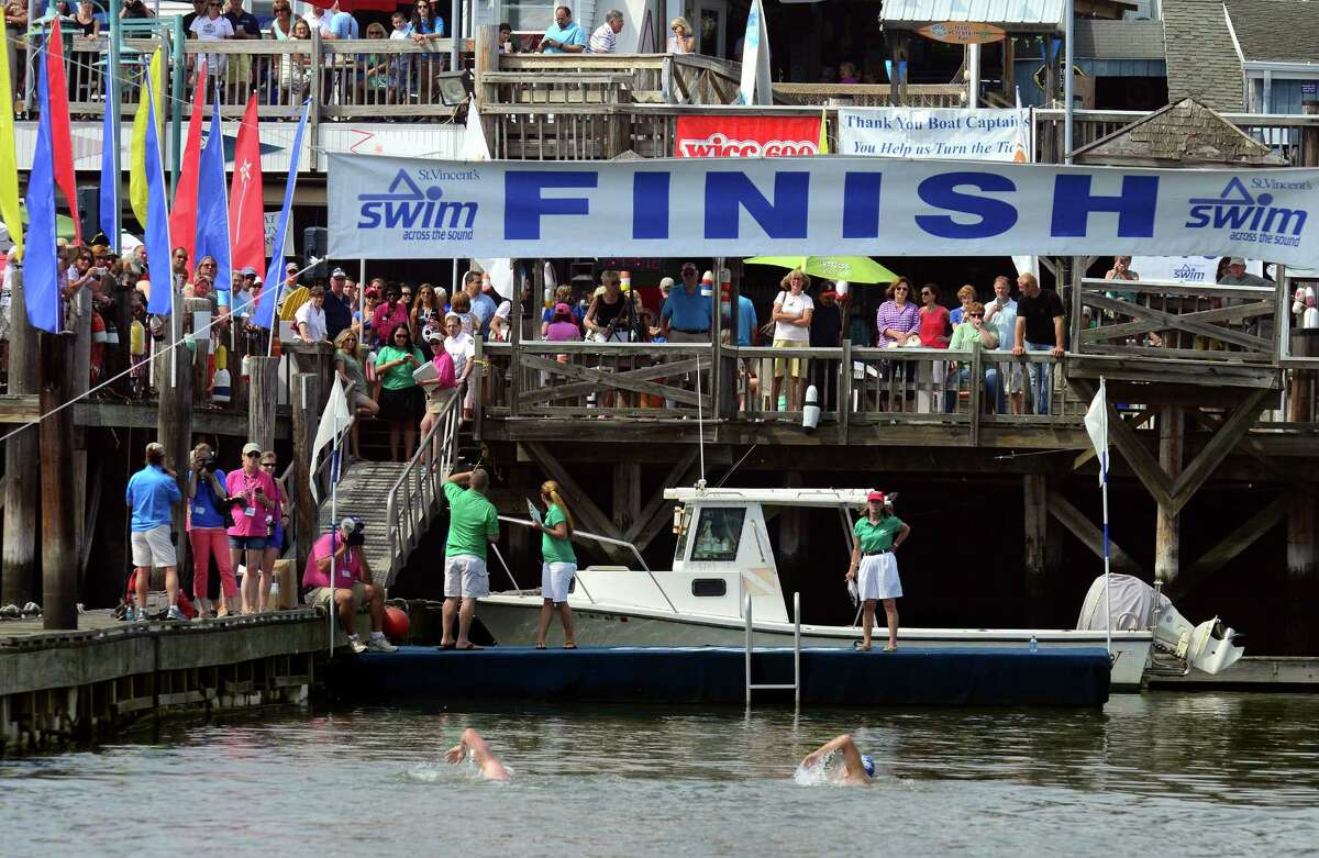 A pair of swimmers reach the finish line together during St. Vincent's 28th Annual SWIM Across the Sound marathon at Captain's Cove Seaport in Bridgeport, Conn., on Saturday July 25, 2015.