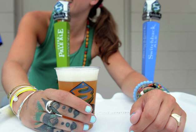 Maegan Gorton serves a cup from Switchback Brewing of Burlington, Vermont during the Sixth Annual Capital Region Craft Brewer's Festival at Joe Bruno Stadium on Saturday July 25, 2015 in Troy, N.Y. (Michael P. Farrell/Times Union) Photo: Michael P. Farrell / 00032764A
