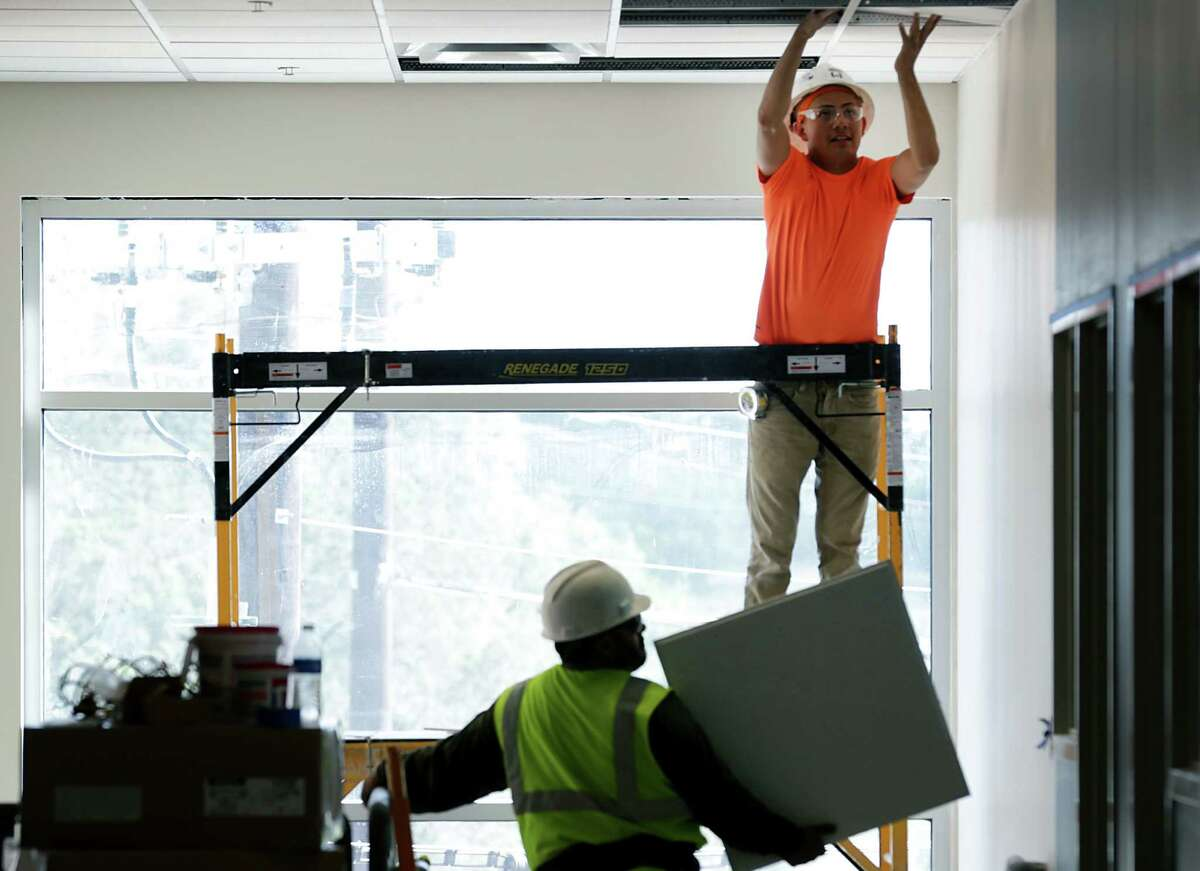 Workers install ceiling tiles at the school. When classes start next month, Great Hearts and four other charter networks will have about 8,500 students in San Antonio.