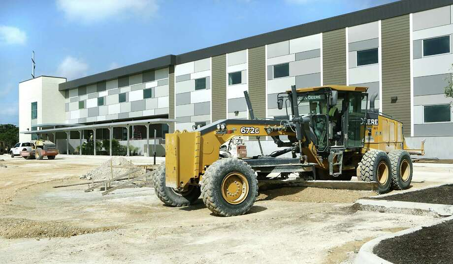 Great Hearts Northern Oaks School on Jones Maltsberger Rd near Loop 1604, is scheduled to be ready for the upcoming school year next month. Workers prepare the front lot for paving on Thursday, July 23, 2015. Photo: Bob Owen, Staff / San Antonio Express-News / San Antonio Express-News
