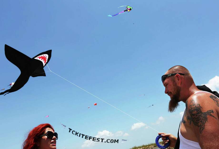Alejandra Terrazas, and Jock Joplin, both of Dickinson, flies his son's shark kite at the Texas City Kite Festival at the Texas City Dike Saturday, July 25, 2015, in Texas City, Texas. The festival featured competitions in kite flying, a kiteboarding hydrofoil race, powered paragliding exhibition, and the worldâÄôs first-ever tanker surfing competition along with vendors providing a variety of food from Gulf Coast BBQ to creative festival and food truck cuisine, drinks and frozen treats to cool off. Photo: Gary Coronado, Houston Chronicle / © 2015 Houston Chronicle