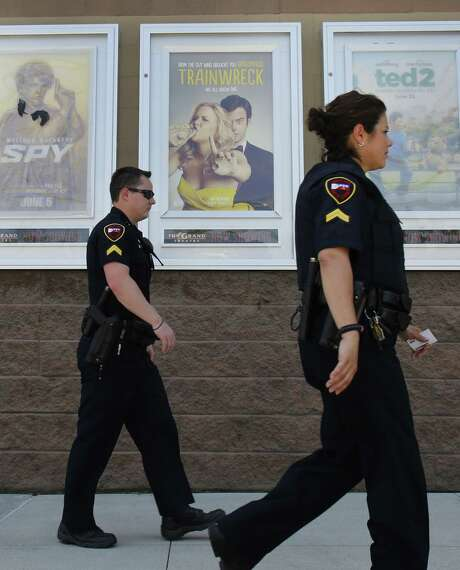 """Police officers walk past a poster of Amy Schumer's movie """"Trainwreck"""" at The Grand Theatre on July 25, 2015 in Lafayette, Louisiana. The troubled """"drifter"""" who randomly killed two women in the Louisiana movie theater and then took his own life has emerged as an anti-government extremist who owned a legally-purchased firearm. AFP PHOTO/YURI GRIPASYURI GRIPAS/AFP/Getty Images Photo: YURI GRIPAS, Stringer / AFP / Getty Images / AFP"""