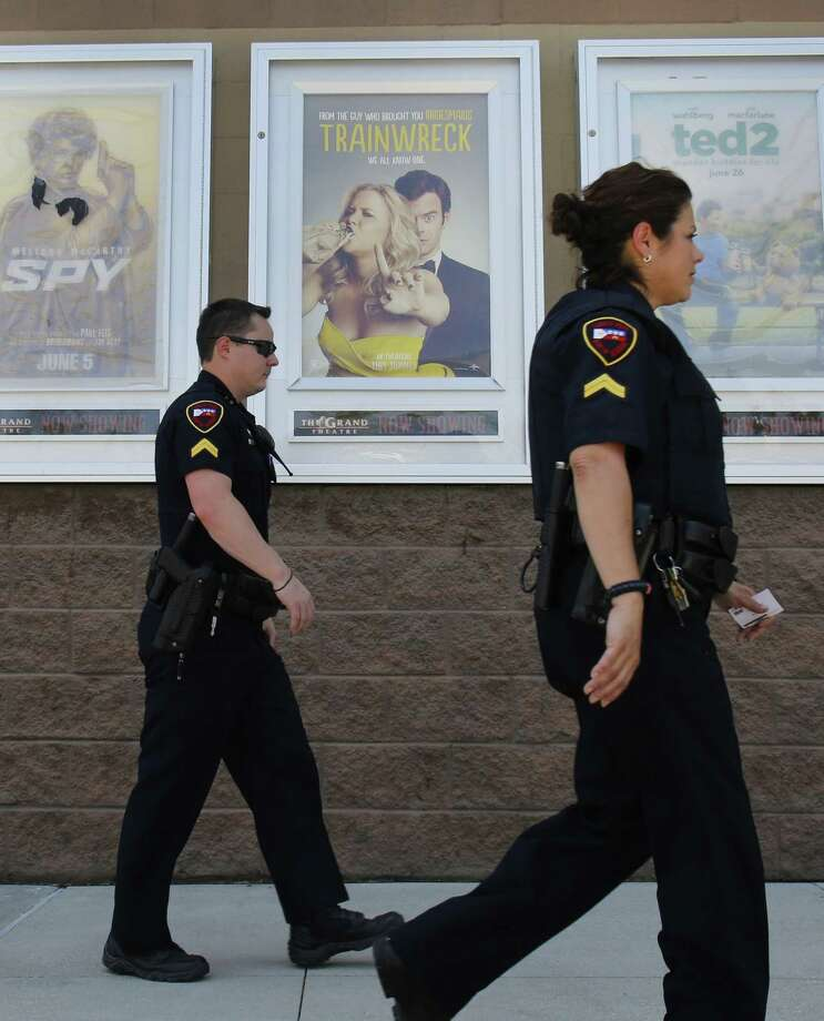 "Police officers walk past a poster of Amy Schumer's movie ""Trainwreck"" at The Grand Theatre on July 25, 2015 in Lafayette, Louisiana. The troubled ""drifter"" who randomly killed two women in the Louisiana movie theater and then took his own life has emerged as an anti-government extremist who owned a legally-purchased firearm. AFP PHOTO/YURI GRIPASYURI GRIPAS/AFP/Getty Images Photo: YURI GRIPAS, Stringer / AFP / Getty Images / AFP"