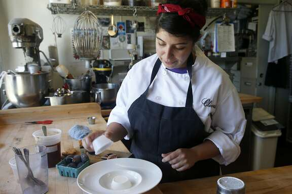 Pastry chef Yakira Batres prepares a panna cotta dessert at Oliveto in Oakland, Calif. on Saturday, July 25, 2015.