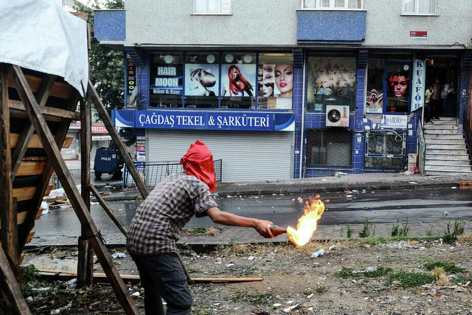 A protester hurls a petrol bomb towards a police car in Istanbul, Friday, July 24, 2015, during clashes between police and protesters denouncing the deaths of 32 people at an suicide bombing Monday in Suruc, southeastern Turkey.  Turkish warplanes struck Islamic State group targets across the border in Syria early Friday, in a strong tactical shift for Turkey which had long been reluctant to join the U.S.-led coalition against the extremist group.  (AP Photo/Cagdas Erdogan, Depo Photos) TURKEY OUT ORG XMIT: XLP118 Photo: Cagdas Erdogan / AP