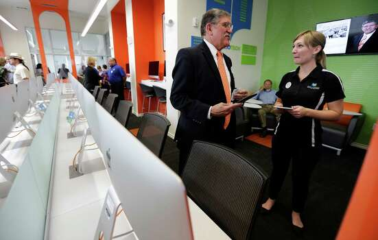 UTSA President Ricardo Romo (left) chats with Bibliotech Head Librarian Ashley Eklof during the celebration of the opening of the second Bibliotech named after Romo at the Gardens of San Juan Square - a San Antonio Housing Authority Community - on Saturday, July 25, 2015. The nation's first all-digital public library, Bibliotech added a second branch in the public housing development located on the city's westside. Romo grew up on the Westside and was honored by having his name emblazoned on the library. Bibliotech gives Bexar County residents access to 38,000 titles which can be accessed via all digital devices and computers. Book titles can also be checked out on e-readers for a two-week period. Gardens of San Juan Square is SAHA's newest mixed-income community that has 539 units. There are currently more than 65,000 registered users of the digital library and over 181,000 on-site visitors to the first location on Pleasanton Road. (Kin Man Hui/San Antonio Express-News) Photo: Kin Man Hui, Staff / San Antonio Express-News / ©2015 San Antonio Express-News