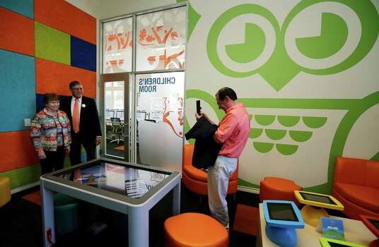 UTSA President Ricardo Romo and his wife, Harriet, pose for a picture by Romo's assistant Albert Carrisalez in the children's room of the second Bibliotech named after Romo at the Gardens of San Juan Square - a San Antonio Housing Authority Community - on Saturday, July 25, 2015. The nation's first all-digital public library, Bibliotech added a second branch in the public housing development located on the city's westside. Romo grew up on the Westside and was honored by having his name emblazoned on the library. Bibliotech gives Bexar County residents access to 38,000 titles which can be accessed via all digital devices and computers. Book titles can also be checked out on e-readers for a two-week period. Gardens of San Juan Square is SAHA's newest mixed-income community that has 539 units. There are currently more than 65,000 registered users of the digital library and over 181,000 on-site visitors to the first location on Pleasanton Road. (Kin Man Hui/San Antonio Express-News) Photo: Kin Man Hui, Staff / San Antonio Express-News / ©2015 San Antonio Express-News
