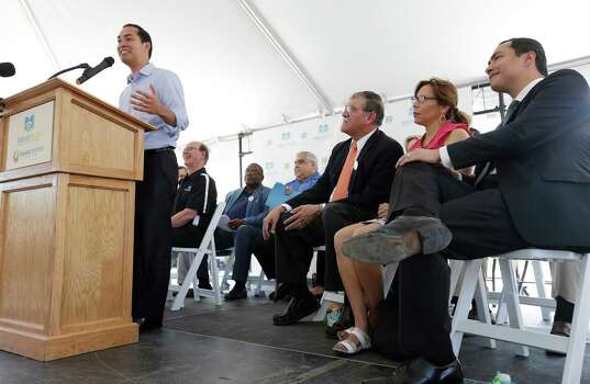 HUD Secretary Julian Castro (left) addresses an audience along with his brother and Congressman Joaquin Castro (from right), councilwoman Shirley Gonzales and UTSA President Ricardo Romo during the celebration of the opening of the second Bibliotech named after Romo at the Gardens of San Juan Square - a San Antonio Housing Authority Community - on Saturday, July 25, 2015. The nation's first all-digital public library, Bibliotech added a second branch in the public housing development located on the city's westside. Romo grew up on the Westside and was honored by having his name emblazoned on the library. Bibliotech gives Bexar County residents access to 38,000 titles which can be accessed via all digital devices and computers. Book titles can also be checked out on e-readers for a two-week period. Gardens of San Juan Square is SAHA's newest mixed-income community that has 539 units. There are currently more than 65,000 registered users of the digital library and over 181,000 on-site visitors to the first location on Pleasanton Road. (Kin Man Hui/San Antonio Express-News) Photo: Kin Man Hui, Staff / San Antonio Express-News / ©2015 San Antonio Express-News