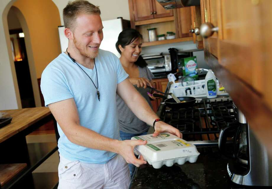 Bryce Bates and friend Maria Rosales spend some time in the kitchen after watching the X Games on television. Photo: Brant Ward / Brant Ward / The Chronicle / ONLINE_YES