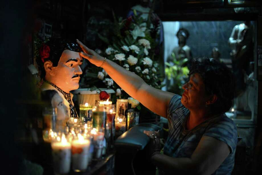 "In this July 20, 2015 photo, Guadalupe Tadeo de Valenzuela prays to folk-saint Jesus Malverde, to heal her sick daughter in the saint's chapel in Culiacan, Mexico. Jesus Malverde is worshipped by many drug traffickers in this region which is also known as the the cradle of drug trafficking in the country. It is in fact, the home state of perhaps the most famous and powerful drug kingpins in the world: Joaquin ""El Chapo"" Guzman, who has escaped from Mexican maximum security prisons twice. He is presently at large. (AP Photo/Fernando Brito) ORG XMIT: MXFB109 Photo: Fernando Brito / AP"
