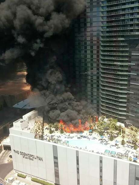 Smokes billows from a fire on the outside pool area of the Cosmopolitan Las Vegas hotel-casino Saturday, July 25, 2015, in Las Vegas. The fire on the pool deck of the hotel and casino caused evacuations and the cause of the fire has not been determined. (Courtney Cyr via AP) MANDATORY CREDIT Photo: Courtney Cyr, UGC / Associated Press / Courtney Cyr