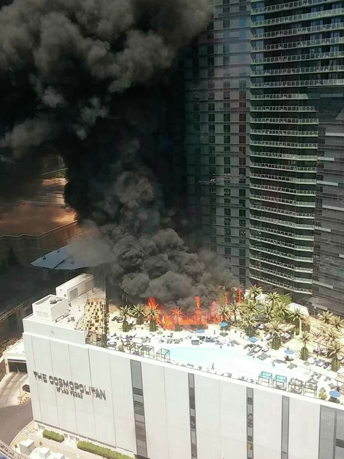 Smokes billows from a fire on the outside pool area of the Cosmopolitan Las Vegas hotel-casino Saturday, July 25, 2015, in Las Vegas. The fire on the pool deck of the hotel and casino caused evacuations and the cause of the fire has not been determined. (Courtney Cyrvia AP) MANDATORY CREDIT Photo: Courtney Cyr, UGC / Associated Press / Courtney Cyr
