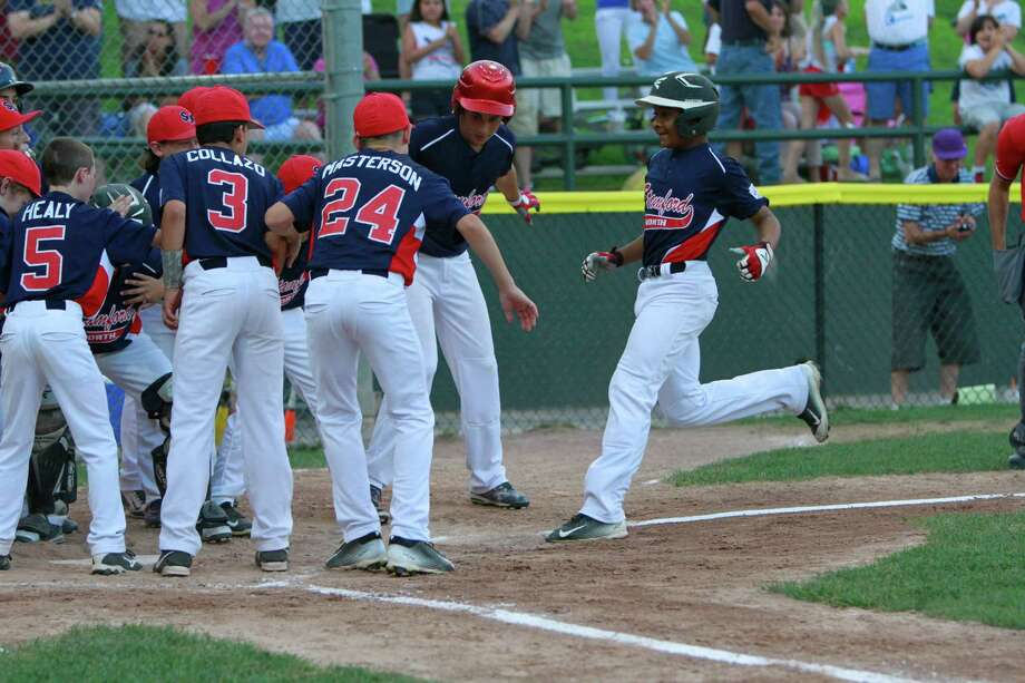 Stamford North's Jayden Dawkins is greeted by teammates following his two run homer in the bottom of the second inning against Hamden in a Division 1 Little League semifinal championship game in Stamford on Saturday, June 25, 2015. Stamford North defeated Hamden 14-4, advancing to Sunday's championship final against Fairfield American. Photo: Matthew Brown, For Hearst Connecticut Media / Connecticut Post Freelance