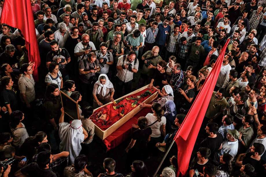 Mourners gather around the body of Gulay Ozarlan, a DHKP-C militant, that was killed in a gunfight with police during a major police sweep that was launched against the outlawed group as well as suspected members of  the outlawed Kurdish rebel group, the PKK and also Islamic State group militants, during her funeral In Istanbul, Saturday, July 25, 2015. Turkish media claimed Ozarlan was wanted by police on suspicion that she planned a suicide attack. (AP Photo/Cagdas Erdogan) TURKEY OUT Photo: Cagdas Erdogan, STR / AP