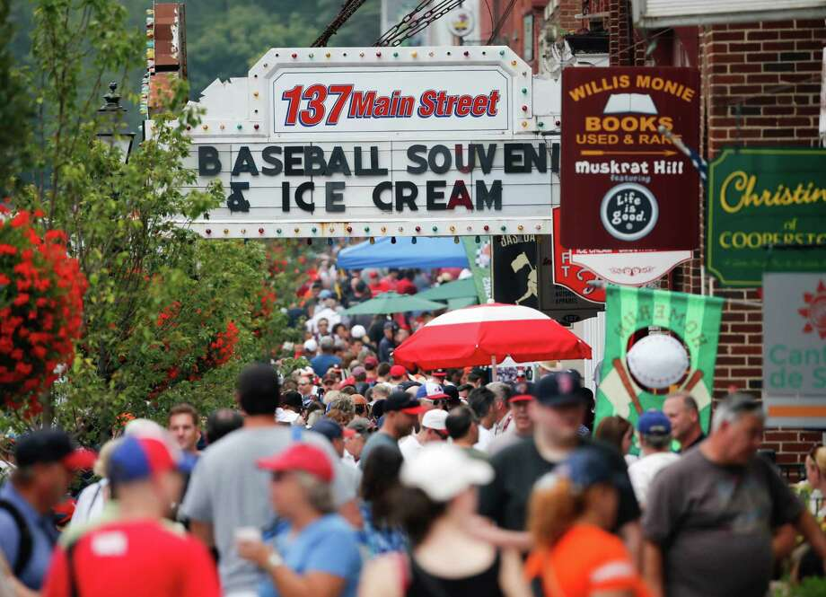 People walk along Main Street on Saturday, July 25, 2015, in Cooperstown, N.Y. The National Baseball Hall of Fame holds its induction ceremony on Sunday. (AP Photo/Mike Groll)  ORG XMIT: NYMG125 Photo: Mike Groll / AP