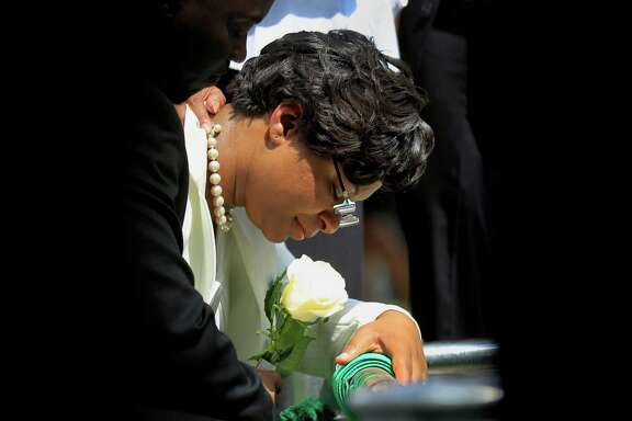 Sandra Bland's sister Sharon Cooper kneels at her  burial site at the Mt. Glenwood Memorial Gardens West cemetery Saturday in Willow Springs, Ill.  An autopsy report released Friday found that Sandra Bland used a plastic trash bag to hang herself three days after a confrontational traffic stop. The 28-year-old woman's family has questioned the findings, saying she was excited about starting a new job and wouldn't have taken her own life. (AP Photo/Christian K. Lee)