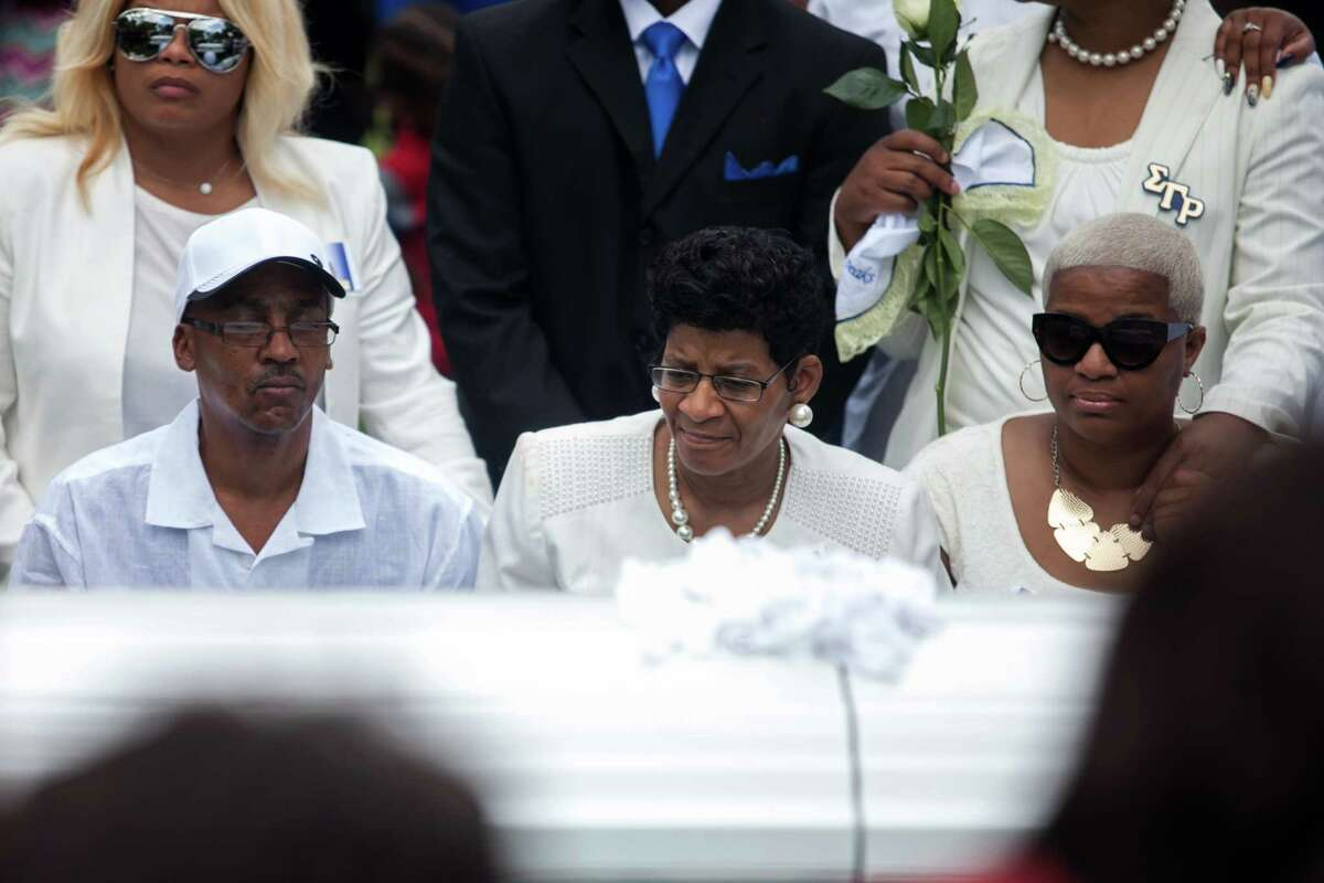"""Sandra Bland's mother, Geneva Reed-Veal, center, and sister Shavon Bland, right, mourn Saturday in Willow Springs, Ill. Reed-Veal remembered a recent road trip with her daughter in which Sandra Bland said, """"Now I know what my purpose is. ... My purpose is to stop all social injustice in the South."""