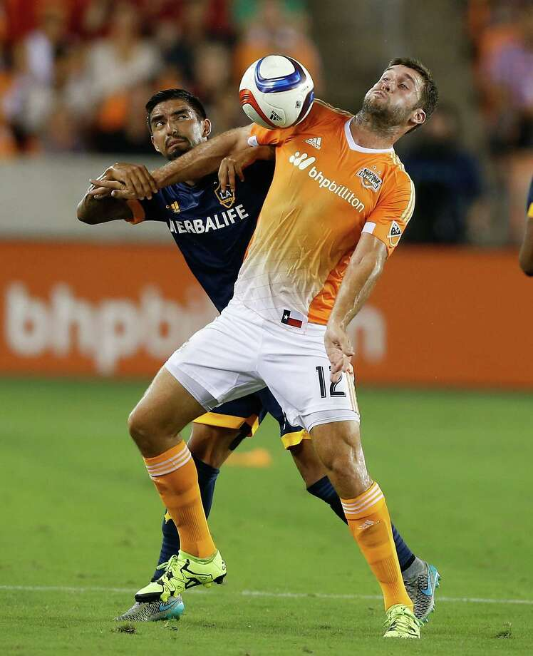 Houston Dynamo forward Will Bruin (12) looks to control the ball as he is pressured by Los Angeles Galaxy defender A.J. DeLaGarza (20) in the first half during a soccer game Saturday, July 25, in Houston. (Bob Levey/For The Chronicle) Photo: Bob Levey, Houston Chronicle / ©2015 Bob Levey