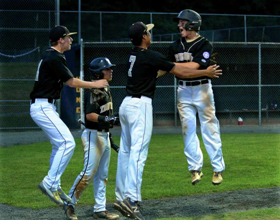 Trumbull's Mike D'Agostino, right, celebrates with teammates after scoring a run, during Babe Ruth tournament action against New Milford in Trumbull, Conn., on Saturday July 25, 2015. Photo: Christian Abraham / Hearst Connecticut Media / Connecticut Post