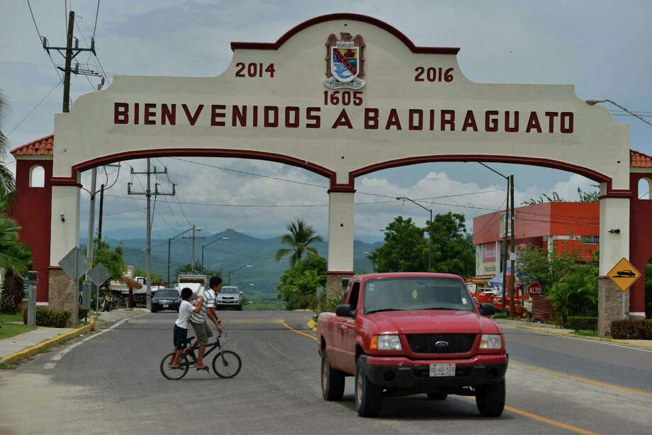 "A car drives past the entrance to the town of Badiraguato, Mexico, last week. The hometown of drug lord Joaquin ""El Chapo"" Guzman, remains mired in poverty. Photo: Fernando Brito, STR / AP"