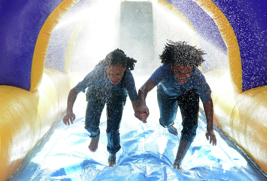 Above, Minnie Phoenix, 9, left, and her sister Makayla, 11,  team up on the water slide during the Community Youth Outreach Youth Fest at Heritage Place in Conroe. At left, Draven Bollinger, 16, shows off his pulling power on the bungee run. Photo: Jerry Baker, Freelance