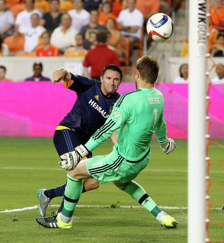 Dynamo goalkeeper Tyler Deric makes a stop on a shot by the Galaxy's Robbie Keane in the first half of Saturday night's game at BBVA Compass Stadium. Photo: Bob Levey, Photographer / ©2015 Bob Levey