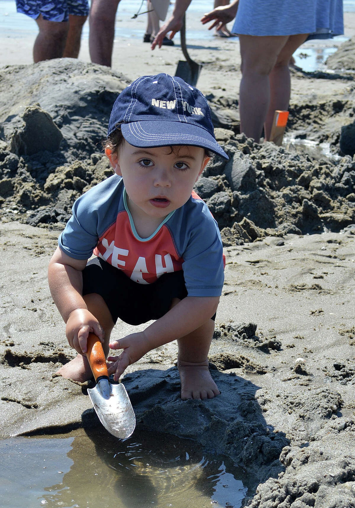 Two-year-old Jake Kimmel Bliman of Fairfield practices his shoveling skills at Penfield Beach in preparation for competing in future sand sculpture contests sponsored by Fairfield PAL.