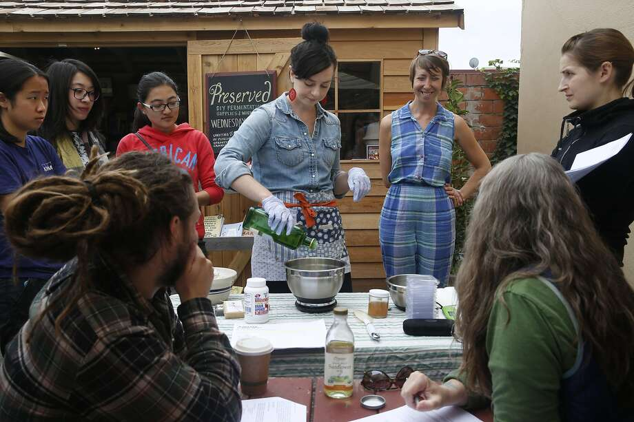 Jeriel Sydney demonstrates how to make soap and salve during a workshop organized by Beth Vecchiarelli (center, right) at Preserved on Piedmont Avenue in Oakland. Photo: Paul Chinn, The Chronicle