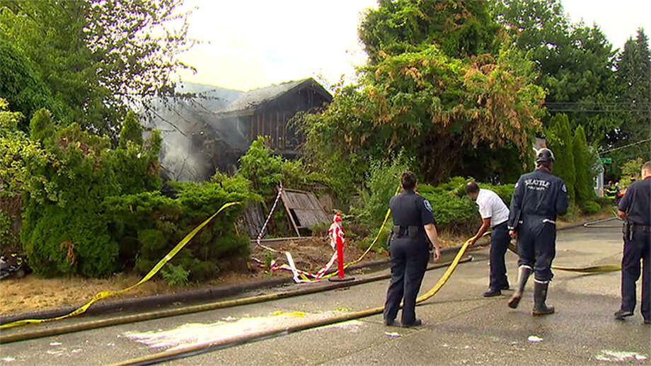 Seattle police and firefighters process the scene of a Beacon Hill house fire Saturday that left one man critically burned. Photo: KOMO