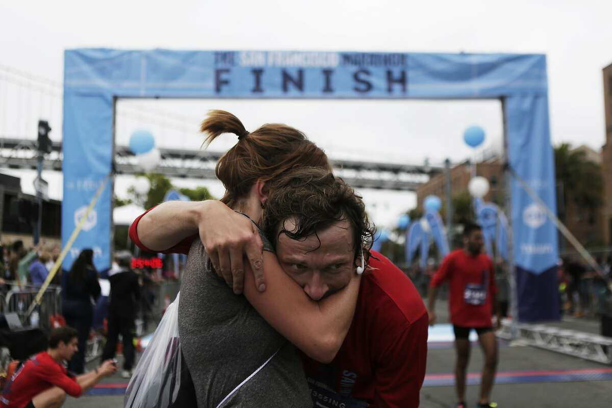 Carolin Dressler and Stefan Messing of Germany embrace each other after crossing the finish line together of the San Francisco Marathon on Sunday, July 26, 2015.