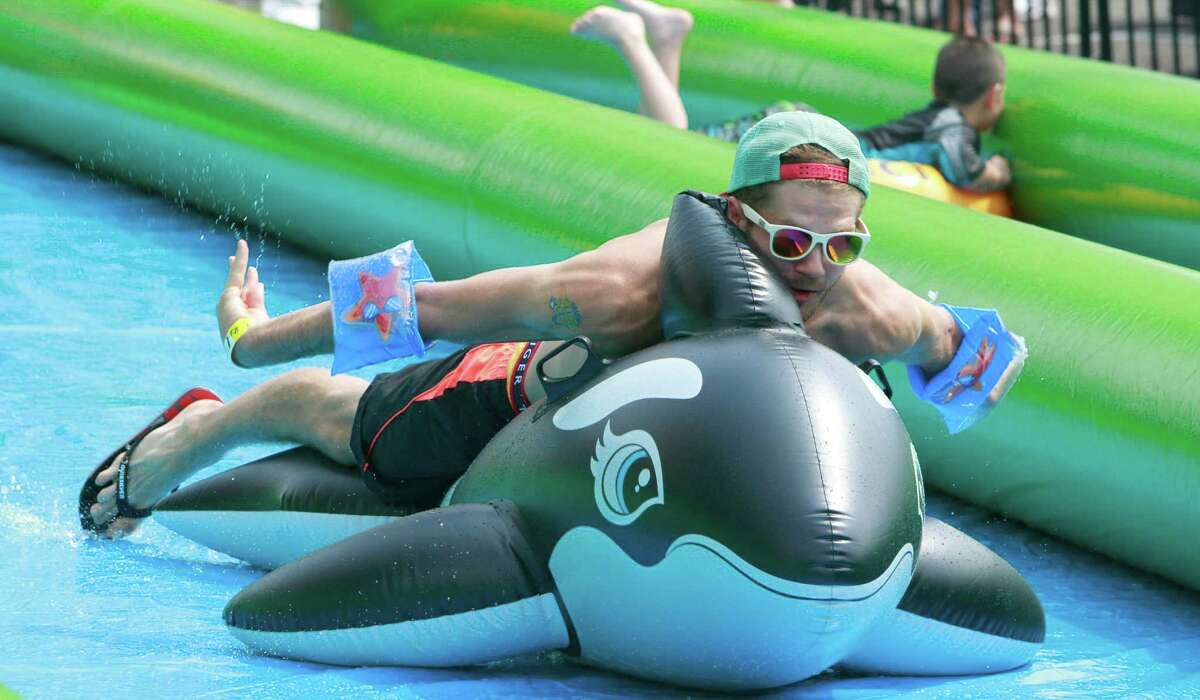 Participants enjoy the thrills of a 1000' Slip-n-Slide set up for the Slide The City event in Stamford on Sunday, June 26, 2015.