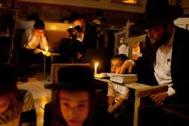 TOPSHOTS Ultra-Orthodox Jewish men use candles to read from the book of Eicha (Book of Lamentations) during the annual Tisha B'Av (Ninth of Av) fasting and a memorial day, commemorating the destruction of ancient Jerusalem temples, in the Ultra-Orthodox neighborhood of Mea Shearim in Jerusalem, on July 25, 2015. Commemorated under the Hebrew calendar as the Ninth of Av, worshippers will gather all night long at the Wailing Wall, the last remaining vestige of the Second Temple, in Jerusalem Old City. AFP PHOTO / GIL COHEN-MAGENGIL COHEN MAGEN/AFP/Getty Images