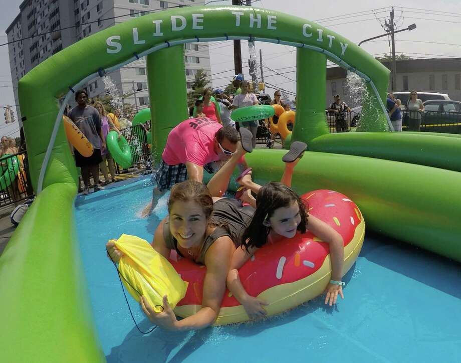 Marni Amsellem, of Stamford, and her daughter Vanessa, 7, double up on a doughnut tube as they slide down Prospect Street during the Slide The City event in Stamford on Sunday. Photo: Matthew Brown / For Hearst Connecticut Media / Connecticut Post Freelance