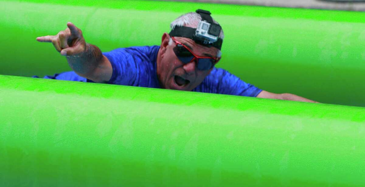 Bobby Valentine, a former American professional baseball player and manager, slides down Prospect Street during the Slide The City event in Stamford on Sunday, June 26, 2015.
