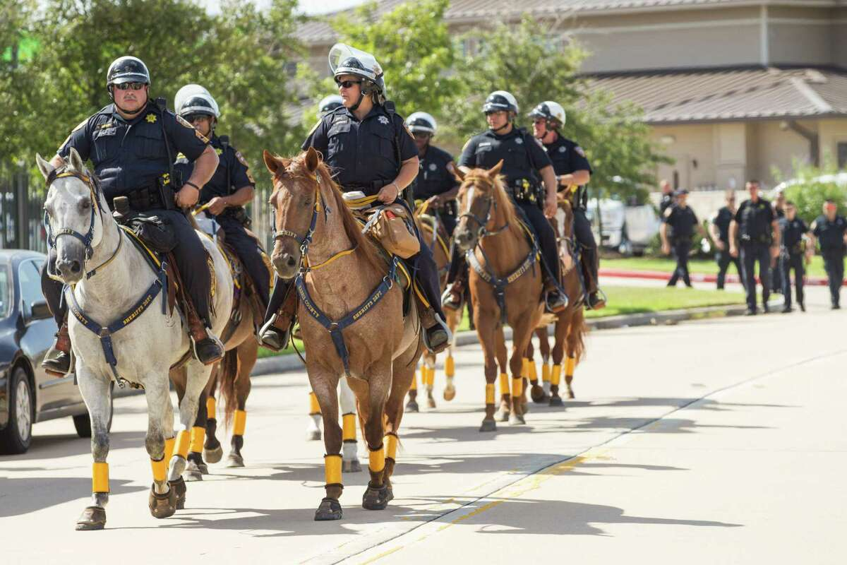 Harris County Sheriff's deputies arrive on horseback before a protest by African-American community leaders calling for the firing and indictment of State Trooper Brian Encinia on Sunday, July 26, 2015, in Katy. The demonstrators gathered at an apartment complex, lined by Harris County deputies on horseback, to protest against the trooper who arrested Sandra Bland.