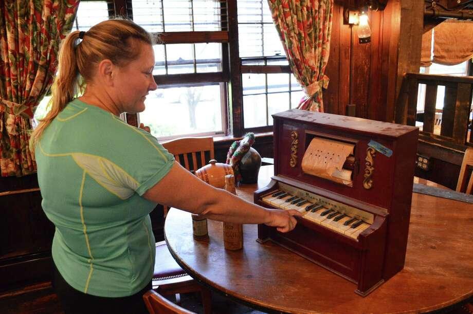 Brigid Van Der Merwe checks out a mini piano. Photo: Jarret Liotta / For Hearst Connecticut Media / Westport News