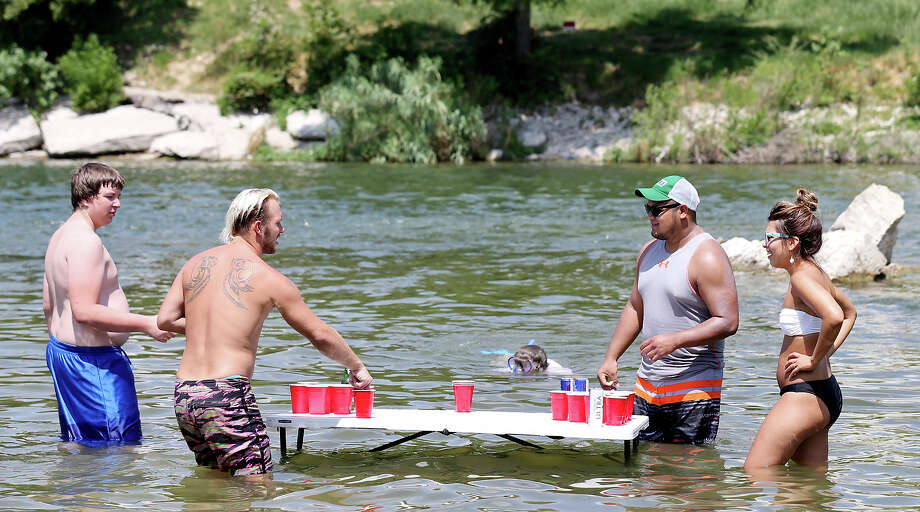 Trying to stay cool people play beer pong in the Guadalupe River at the Faust Street Bridge Sunday July 26, 2015 in New Braunfels , Tx. Photo: Edward A. Ornelas, San Antonio Express-News / © 2015 San Antonio Express-News