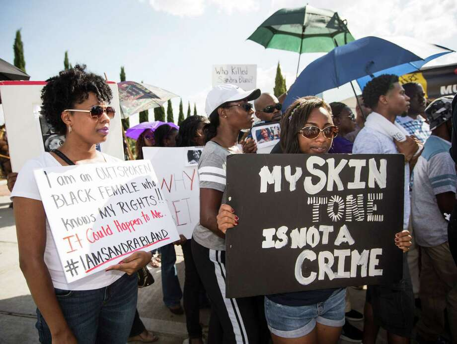 Demonstrators call for the firing and indictment of State Trooper Brian Encinia during a protest on Sunday, July 26, 2015, in Katy. The demonstrators gathered at an apartment complex, lined by Harris County deputies on horseback, to protest against the trooper who arrested Sandra Bland. Photo: Brett Coomer, Houston Chronicle / © 2015 Houston Chronicle
