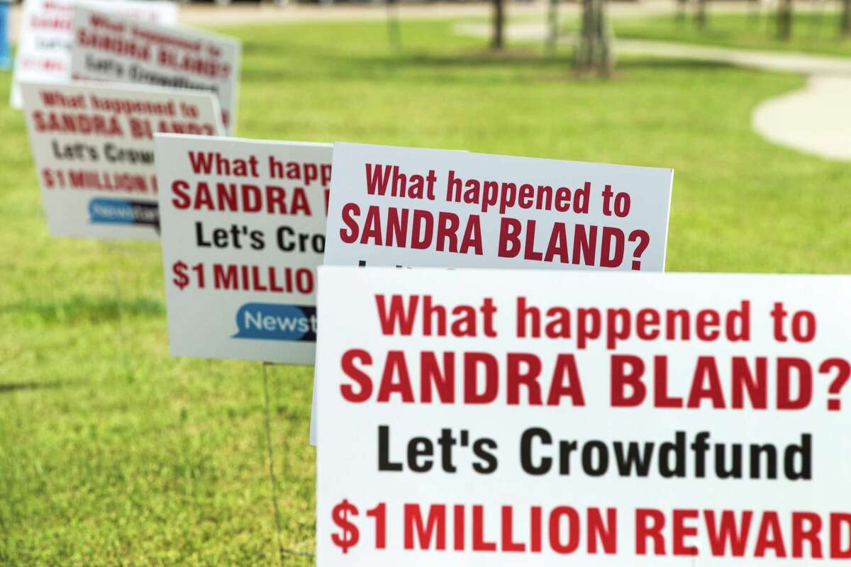 Signs line the street during a protest calling for the firing and indictment of State Trooper Brian Encinia on Sunday, July 26, 2015, in Katy. The demonstrators gathered at an apartment complex, lined by Harris County deputies on horseback, to protest against the trooper who arrested Sandra Bland.