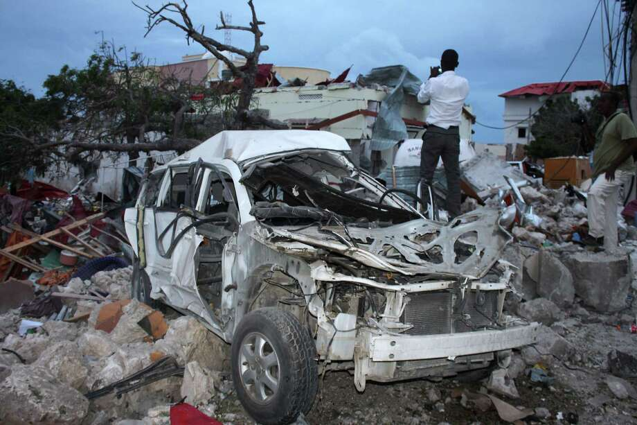 A man stands over rubble next to a destroyed vehicle near the damaged Jazeera Palace hotel after a suicide explosion in Mogadishu on Sunday. Photo: -, Stringer / AFP